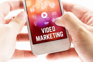 Close up Two hand holding mobile phone with Video marketing word and icons, Online Digital Marketing concept